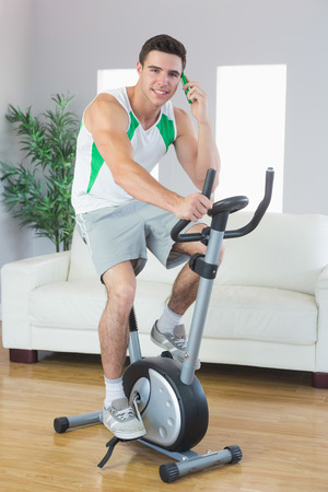 Cheerful handsome man training on exercise bike phoning in bright living room photo