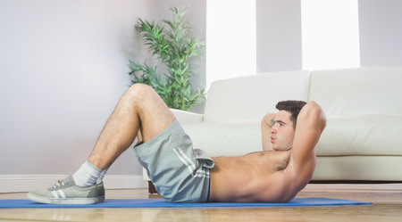 Sporty handsome man doing sit ups in bright living room photo