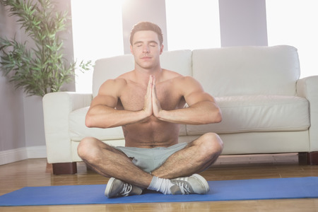 Peaceful handsome man meditating in bright living room photo