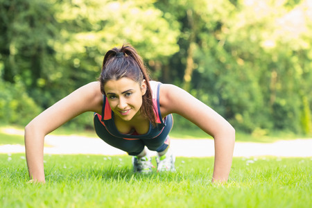 plank position: Smiling fit woman doing plank position looking at camera on the grass