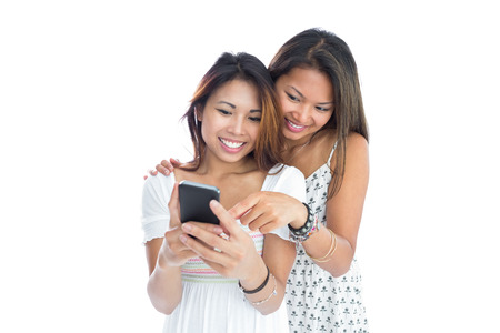 Two young sisters using smartphone on white background photo