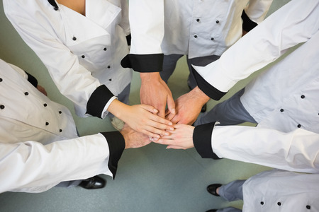 hotel kitchen: Five chefs joining hands in a circle wearing uniforms