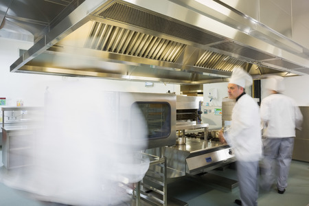 Team of chefs working in a kitchen at a hurried pace photo