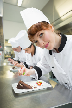 Happy chef garnishing dessert plate standing in a kitchen photo