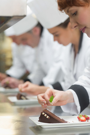 Team of young chefs in a row garnishing dessert plates in commercial kitchen photo