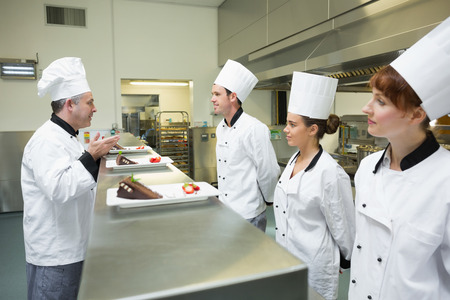 judging: Three chefs presenting their dessert plates to the head chef in busy kitchen