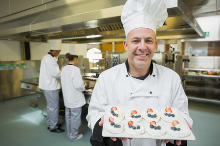 Smiling chef presenting proudly plate of meringues in busy kitchen photo