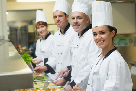 Four chefs smiling at camera while working at serving trays in busy kitchen photo