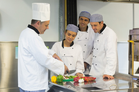 Smiling head chef teaching how to slice vegetables to his students in kitchen photo