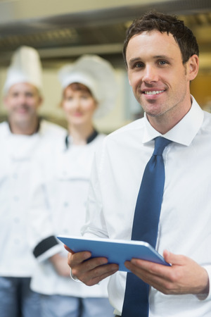 Young restaurant manager holding his tablet  smiling at the camera  photo