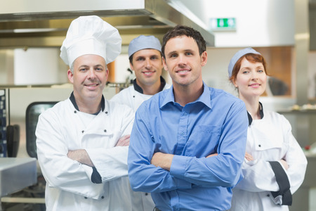 Young manager posing with some chefs in a kitchen  photo