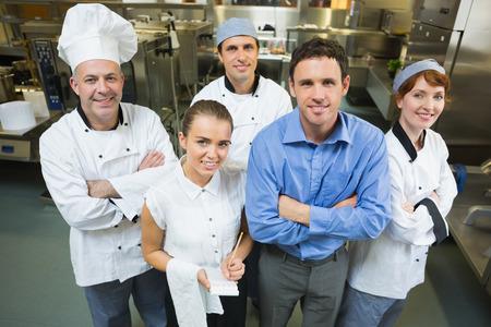 Knappe manager poseren met sommige chefs en serveerster in een keuken Stockfoto