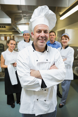 Head chef posing with his team behind him in restaurant kitchen photo