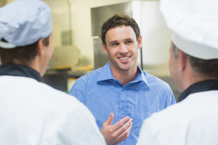 Young smiling manager talking to the staff standing in a kitchen Stock Photo