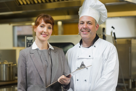 Mature head cook posing with the female manager in a professional ktichen photo