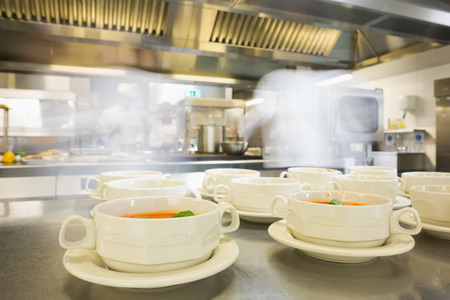 Bowls filled with hot soup in a professional kitchen photo