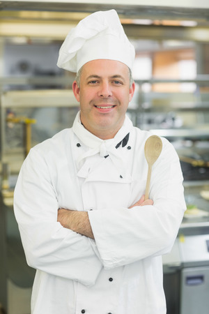 Mature head chef smiling at camera holding a wooden spoon photo