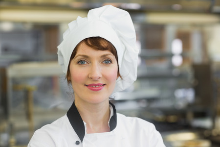 Happy female chef posing in a kitchen smiling at the camera  photo