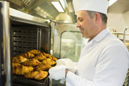 bakery oven: Mature baker putting some croissants into an oven wearing a uniform