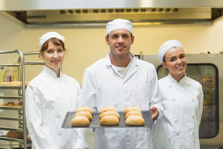 Young male baker holding a baking tray with rolls on it posing with colleagues photo