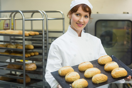 bakery oven: Happy female baker showing some rolls on a baking tray smiling at the camera