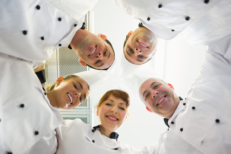 Five smiling chefs standing in a circle looking down at camera photo