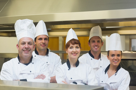 Five chefs posing with crossed arms smiling at the camera photo