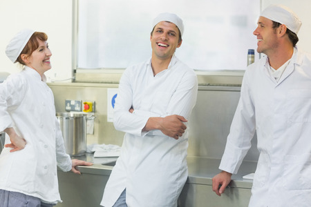 Three chatting bakers standing in a bakery while having fun and laughing photo
