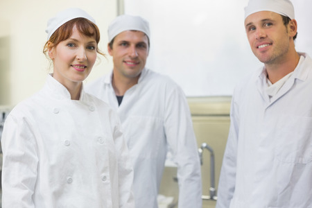 Three bakers posing in a kitchen smiling at the camera photo