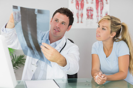 Content doctor showing a patient something on xray in bright office photo