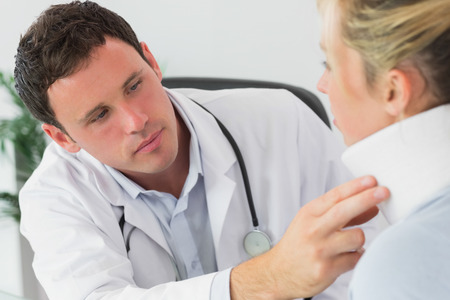 serious doctor: Serious doctor examining neck of a patient in bright office