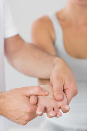 Physiotherapist examining patients hand in bright office photo