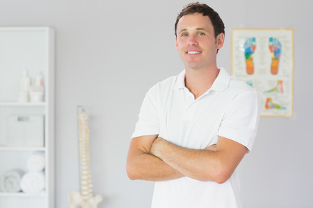 Handsome happy physiotherapist standing with arms crossed in bright office photo