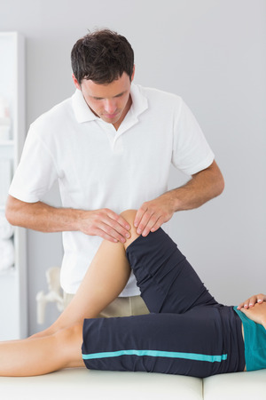 Physiotherapist examining knee of a patient in bright office photo