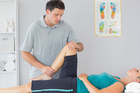 Attractive physiotherapist controlling knee of a patient in bright office photo