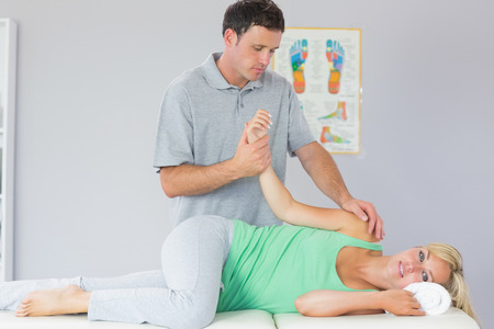 manipulating: Handsome physiotherapist manipulating patients arm in bright office
