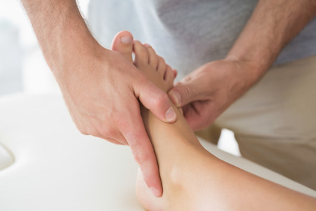Physiotherapist massaging patients foot in bright office photo