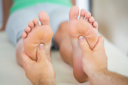 Physiotherapist giving a patient a foot massage in bright office
