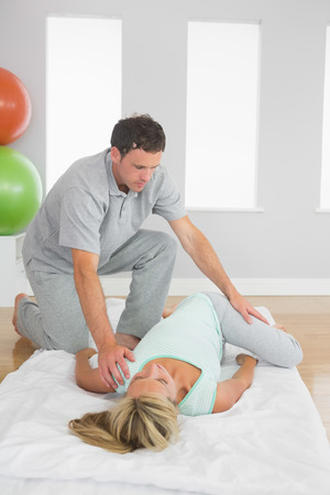 Physiotherapist examining patients hips on a mat on the floor in bright room photo