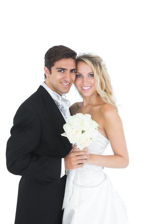 Dolce coppia di sposi in posa in possesso di un mazzo di fiori bianco su sfondo bianco Archivio Fotografico
