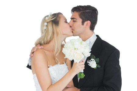 Young couple holding a white bouquet and kissing each other  photo
