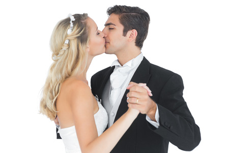 Young married couple dancing viennese waltz kissing each other on white background photo