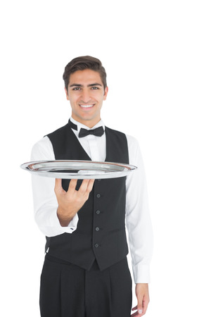Young waiter presenting an empty tray smiling at camera photo