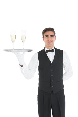Young waiter presenting a silver tray smiling at camera photo