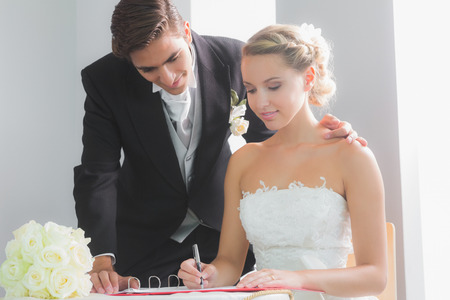 Young blonde bride sitting at table signing wedding register being watched by her husband photo