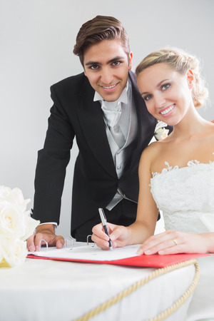 Portrait of pretty young couple signing wedding contract smiling at camera photo