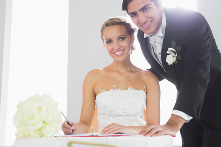 Attractive couple signing wedding register smiling at camera photo