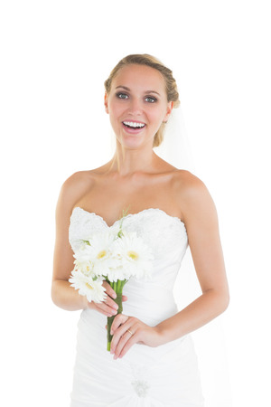 Laughing young bride posing and holding a bouquet looking at camera photo
