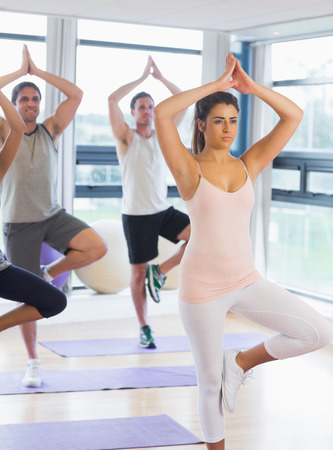 Fitness class and instructor standing in tree pose at  exercise studio photo