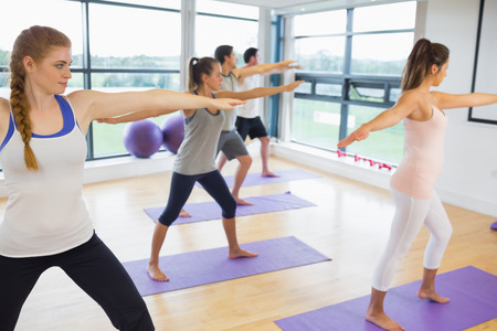 Full length of sporty people stretching hands at yoga class in fitness studio photo